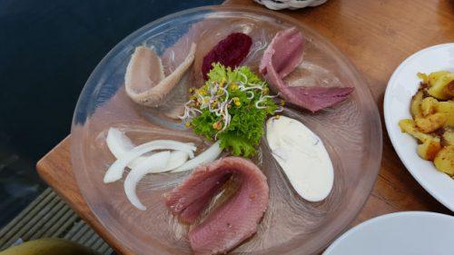 Bild - ein Teller mit verschiedenen Heringssorten Sauce und Zwiebel