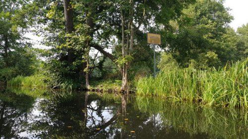 Bild von einem Ortseingangsschild mitten im Grün eines Wasserkanals